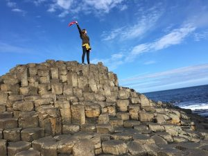 Woman standing waving red towel on rocky structure